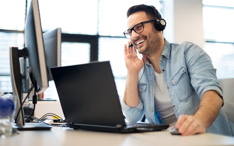 Laughing man on headset while working