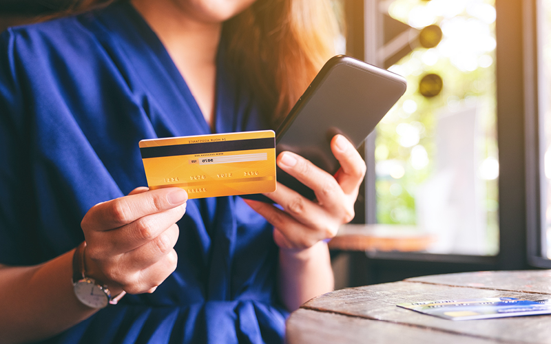 Woman using her credit card on a cellphone